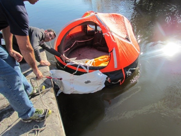 Water deployment of life raft to test activation system